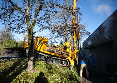 Setting up the drill rig on a steep slope. Ensuring the tract-mounted rig is secure and safe to drill.