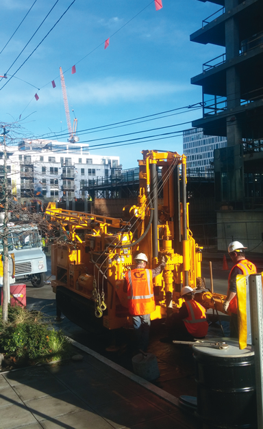 The track-mounted CME 55LCX rig drilling in Seattle beneath low handing power lines.