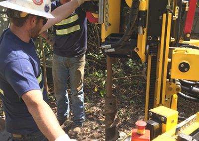 New, limited access rubber track drilling rig conducting soil sampling in tight quarters in dense brush.