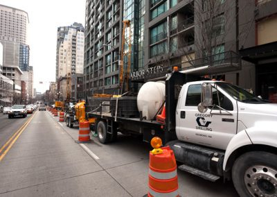 Urban drilling on a busy city street surrounded by Class A commercial buildings.