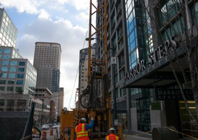 Drilling beneath high rises on a busy city street.
