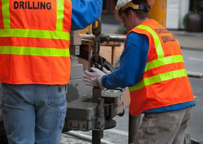 Drilling using a track-mounted drill rig on a busy urban street.