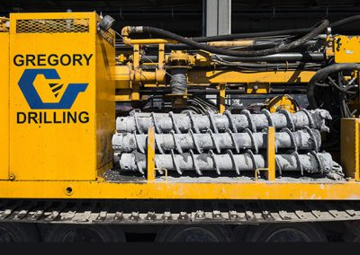 Hollow stem augers on a track-mounted mud rotary drill rig.