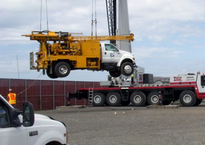 Loading a drill rig onto a barge for over-the-water drilling.