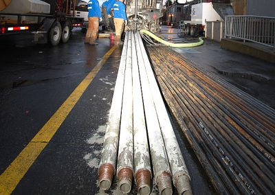 Drill pipe ready to be loaded onto a Gregory Drilling flatbed trailer and removed from the drill site.