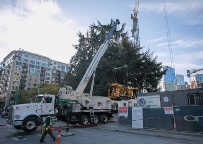 A 60 ton crane hoists the CME 55 LCX drill rig from the street toward the drill site.